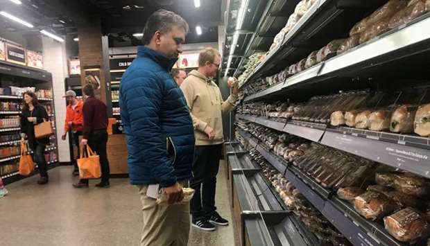"Customers browse packaged wraps, sandwiches and salads at Amazon's new ""grab-and-go"" store in Seattl"