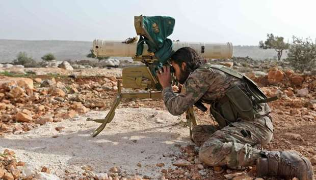 A Turkish-backed Syrian rebel fighter looks through the scope of a rocket launcher at a monitoring p
