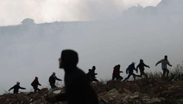 Palestinian protesters run for cover from tear gas fired by Israeli forces during clashes near the J