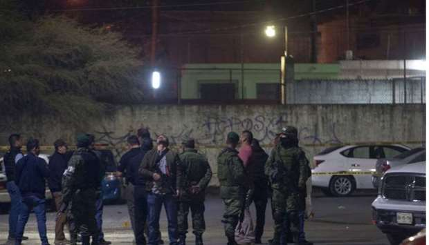 Members of the Mexican army monitor the area where seven people were killed inside a house