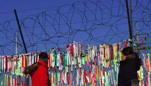 Visitors walk past a military fence covered with ribbons with inscriptions calling for peace and reu