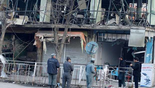 Afghan policemen inspect the site of a bomb attack in Kabul, Afghanistan