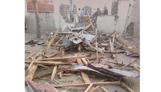 People stand near the damage following an attack on a mosque in the town of Gamboru in Borno state,