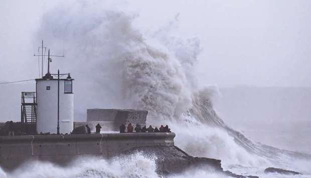Large waves lash the lighthouse and seawall at Porthcawl in south Wales yesterday.