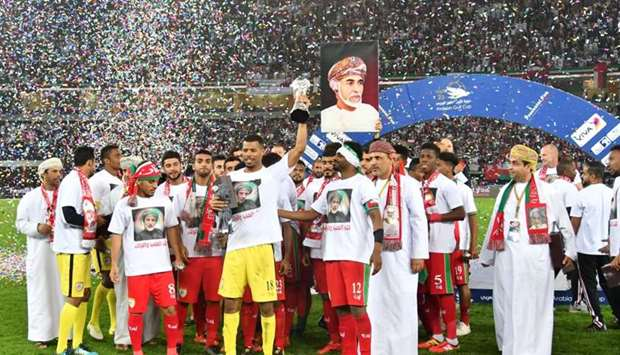Oman's goalkeeper Fayez Issa al-Rusheidi holds the trophy next to his teammates after his team won t
