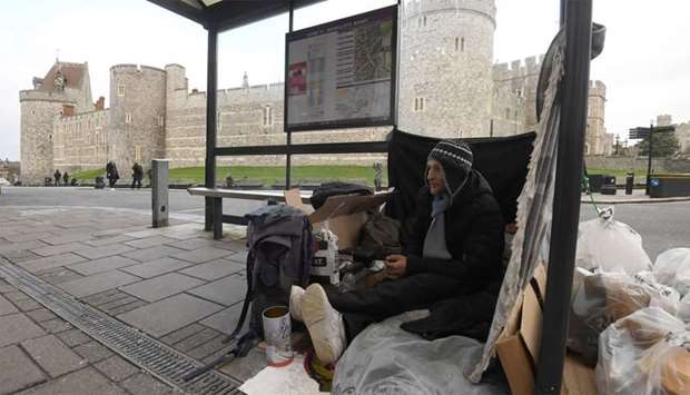 Stuart, a homeless man, sits under a bus shelter where he sleeps opposite Windsor Castle in Windsor,