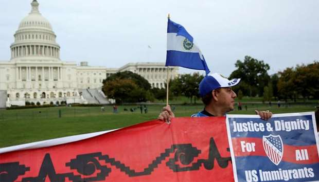 Salvadoran man holds flag and sign during a protest rally for immigrants rights on Capitol Hill in W