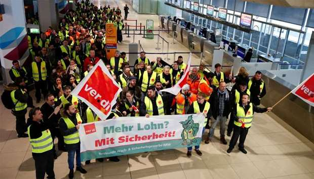 Security personal of the Cologne-Bonn Airport wave flags of German union Verdi during a strike in Co