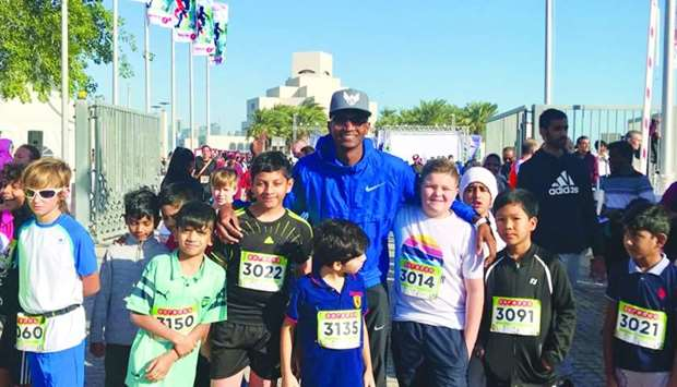 Qatari World high jump champion Mutaz Barshim with a group of child runners who joined the Ooredoo D