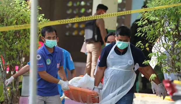 Paramedics take away a body after four Thai civil defence volunteers were shot and killed outside of