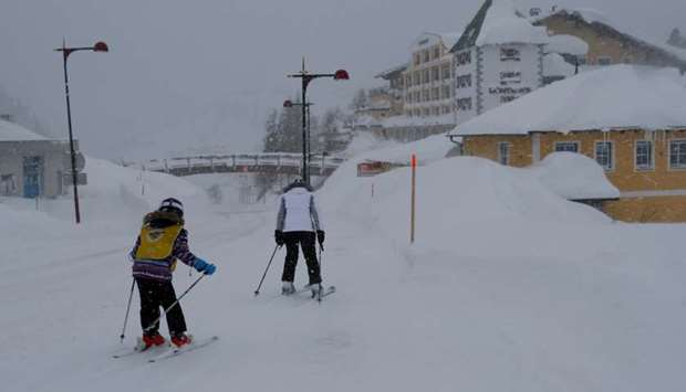Skiers make their way down a road after heavy snowfall in the Austrian Alpine resort of Obertauern