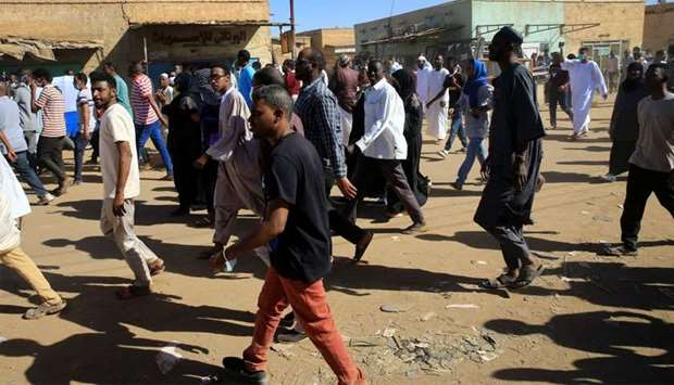Sudanese demonstrators march along the street during anti-government protests after Friday prayers i
