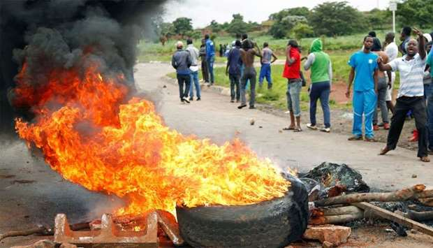 Protesters stand behind a burning barricade during protests on a road leading to Harare