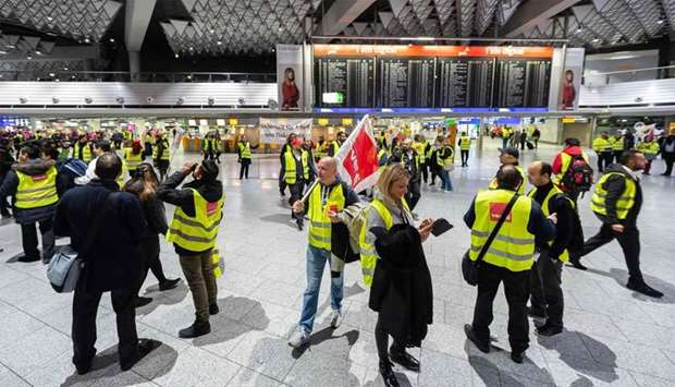 Security staff members wearing vests with the logo of German union verdi stand in front of a board d