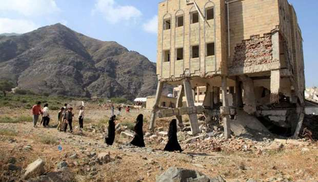 People walk past a school, damaged during the ongoing war in Taiz, Yemen