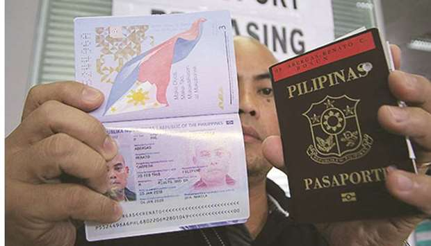 A man shows his newly released passport at the Department of Foreign Affairs office in Pasay City.