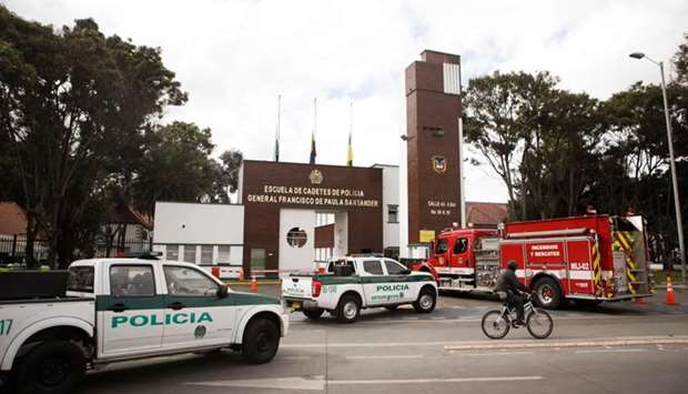Police cars and a firetruck are seen outside General Santander Police Academy in Bogota, a day after