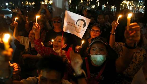 A placard mocking Thailand's Prime Minister Prayuth Chan-o-cha as Pinocchio is seen as activists hol