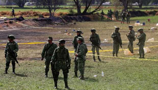 Soldiers are seen at the site where a fuel pipeline ruptured by suspected oil thieves exploded, in t
