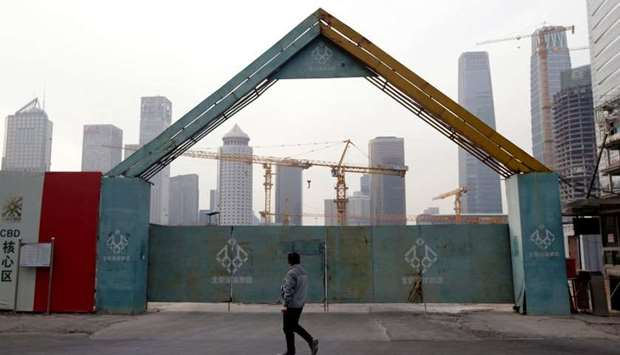 A man walks outside the construction sites in Beijing's central business area
