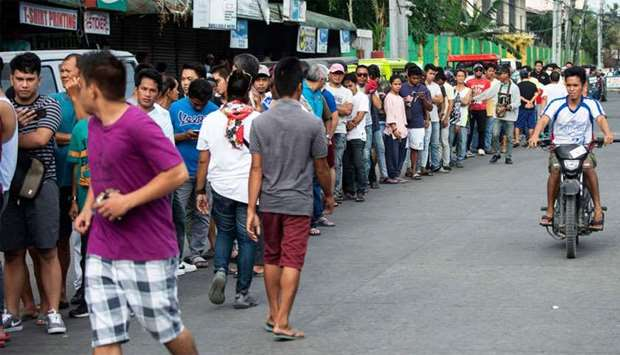 People line up to cast their ballot at a voting precinct in Cotabato on the southern Philippine isla