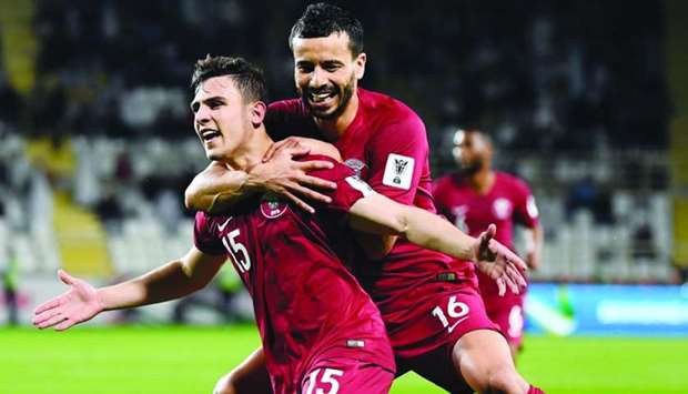 Qatar's Bassam al-Rawi (left) celebrates his goal against Iraq with Boualem Khoukhi
