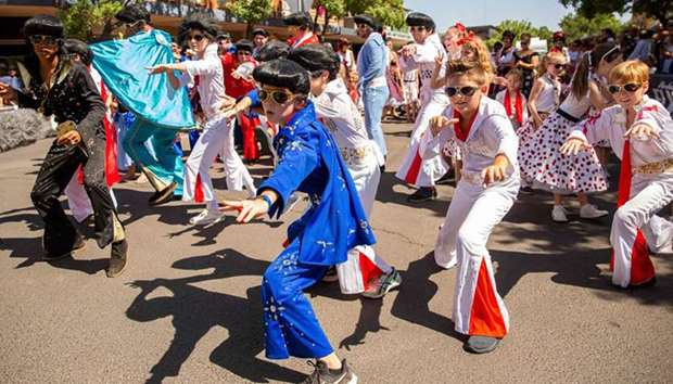 Children dressed as Elvis dancing in the street during the 2019 Parkes Elvis Festival in Parkes