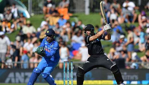 New Zealand's Doug Bracewell (R) plays a shot as India's wicketkeeper Mahendra Singh Dhoni (L) looks