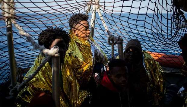 rescued migrants from a group of 47, wrapped in survival blankets and including an underaged (C) are