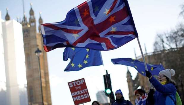 Anti-Brexit activists hold placards and wave Union and EU flags as they demonstrate near the Houses