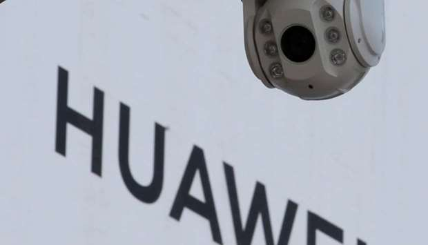A surveillance camera is seen next to a sign of Huawei outside a shopping mall in Beijing, China