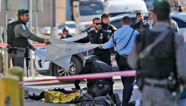Israeli forces cover the body of an alleged attacker lying on the ground