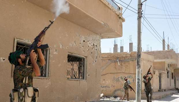 Kurdish fighters from YPG fire rifles at a drone operated by Islamic State militants in Raqqa