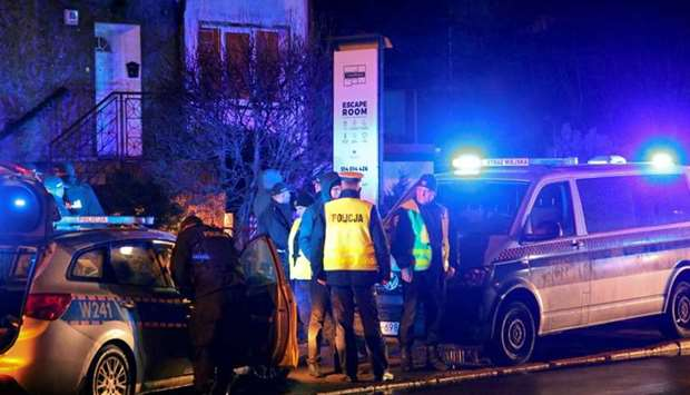 Police officers are seen at the site of a fire which broke out in an escape room yesterday in Koszal