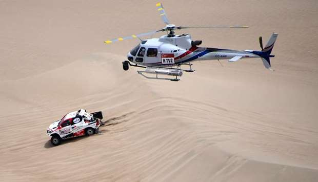 Toyota's driver Nasser Al-Attiyah of Qatar and his co-driver Mathieu Baumel of France compete