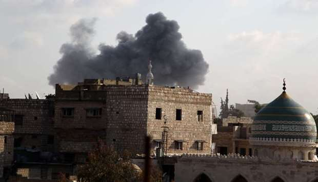 Smoke billows above buildings in the town of Maaret Al-Numan in Syria's northwestern Idlib province