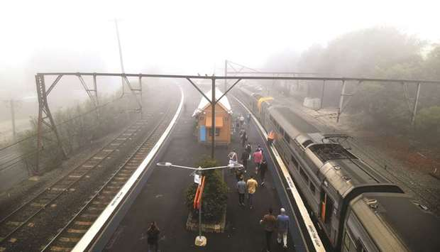 Train passengers alight at the Katoomba railway station as fog mixed with bushfire smoke fills the s