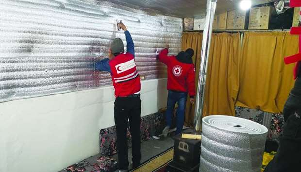 QRCS personnel installing thermal insulation inside the tents of Syrian refugees in Lebanon.