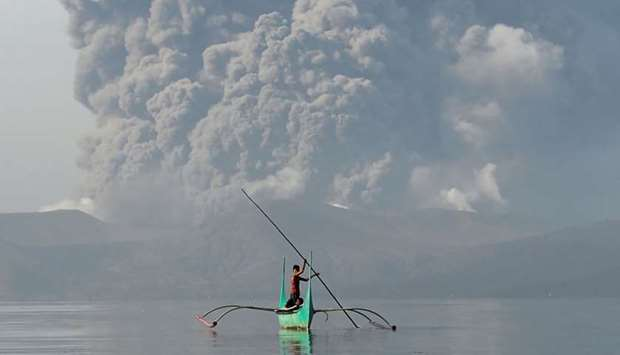 A youth living at the foot of Taal volcano rides an outrigger canoe while the volcano spews ash as s