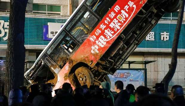 Chinese rescuers watching as a car is lifted out after a road collapse in Xining in China's northwes
