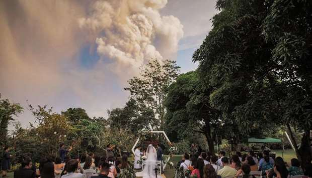 Chino and Kat Palomar attend their wedding ceremony as Taal Volcano sends out a column of ash in the