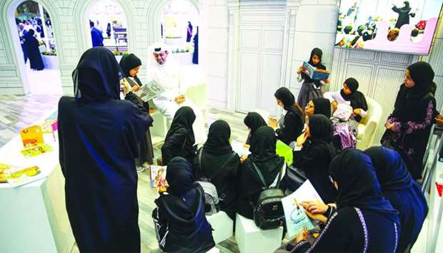 Children read books at the QNL pavilion at DIBF.