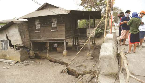 Residents look at a neighbour's house standing on a fissure, caused by tremors caused by Taal volcan