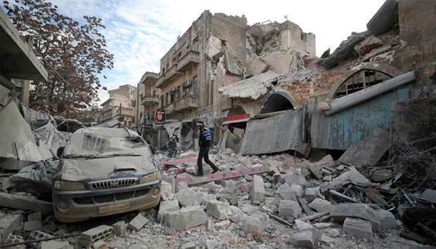 A Syrian walks on the rubble of a building following a regime air strike on Ariha town in Syria's la