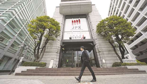 A pedestrian walks past the Tokyo Stock Exchange building in Tokyo. The TSE ended 0.5% higher 24,041