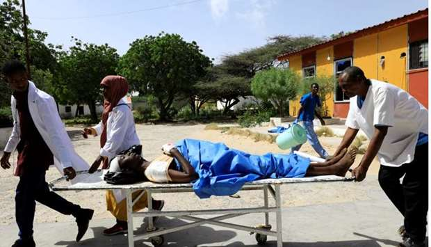 Paramedics at the Madina hospital assist an unidentified man injured in an explosion in Afgoye, as h
