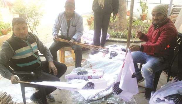 Aam Aadmi Party workers prepare banners and posters to be used during campaigns for the Delhi assemb