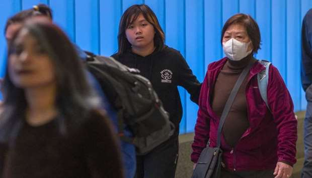 woman arriving on an international flight to Los Angeles International Airport wears a mask on the f