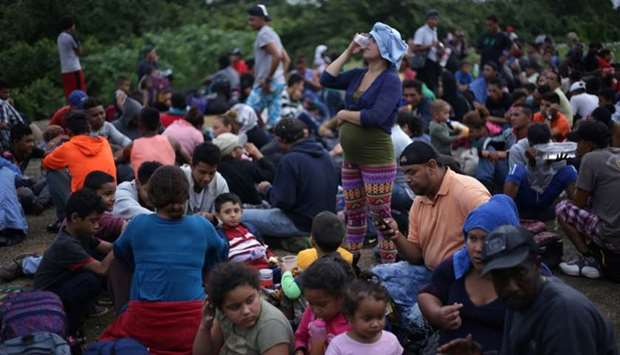 Migrants from Central America, part of a caravan travelling to the U.S., wait to cross into Mexico a