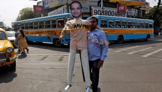 A demonstrator holds an effigy depicting billionaire jeweller Nirav Modi during a protest in Kolkata